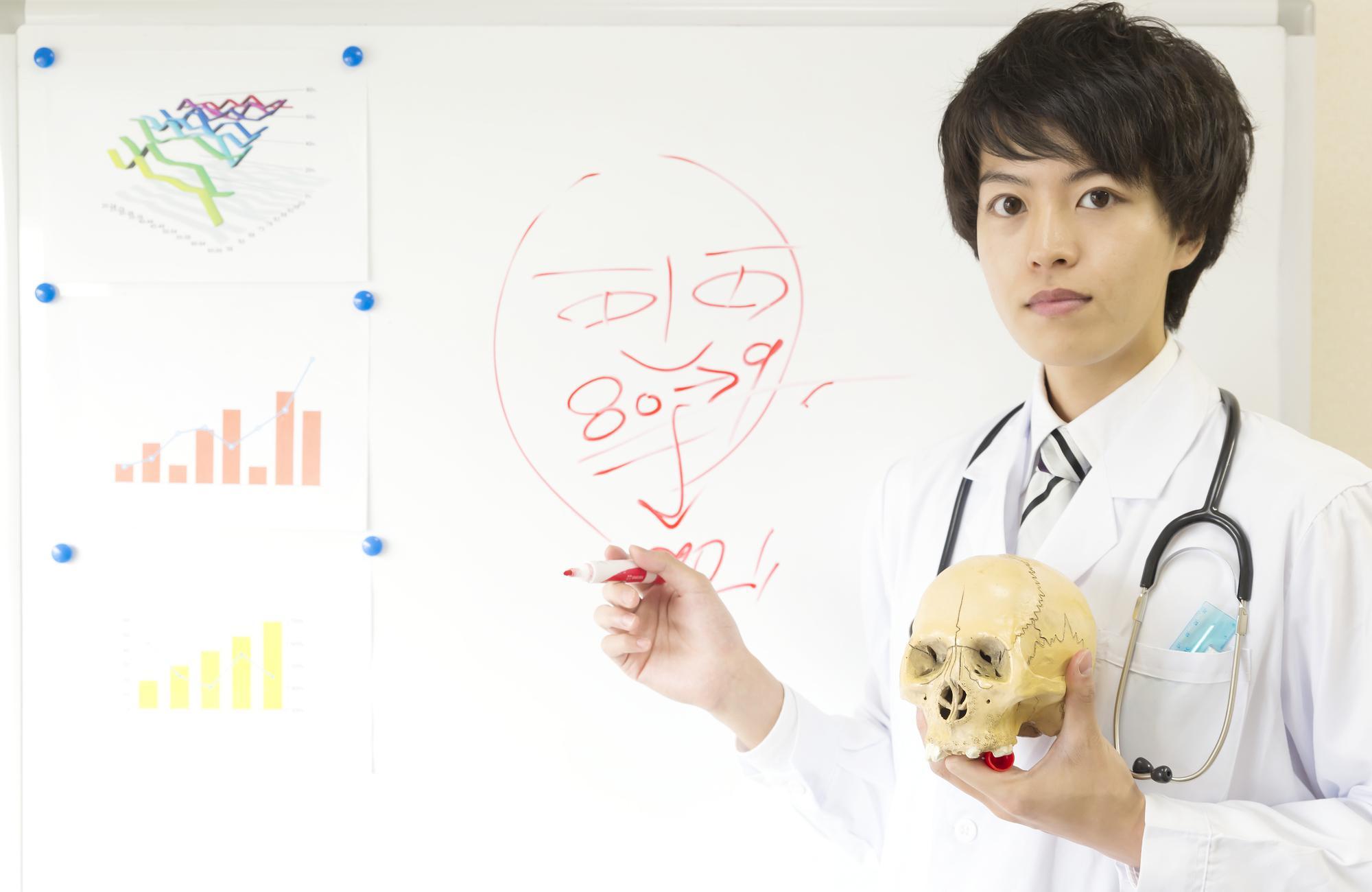 頭蓋骨の模型を持つ医師